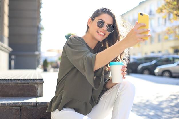 Smiling beautiful brunette woman walking outdoors by street, take selfie by mobile phone, drinking coffee.