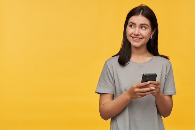 Улыбающаяся красивая брюнетка молодая женщина в серой футболке использует мобильный телефон и смотрит в сторону на пустое пространство над желтой стеной