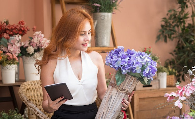 Smiling beautiful business woman check order in flower shop