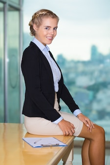 Smiling Beautiful Business Woman Sitting on Table