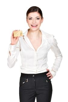 La bella donna sorridente di affari in una camicia bianca tiene la carta di credito - isolata su bianco.