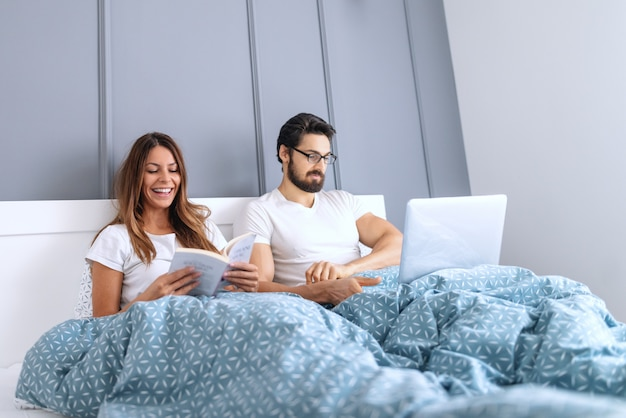 Smiling beautiful caucasian brunette reading book in bed while her husband with eyeglasses using laptop.