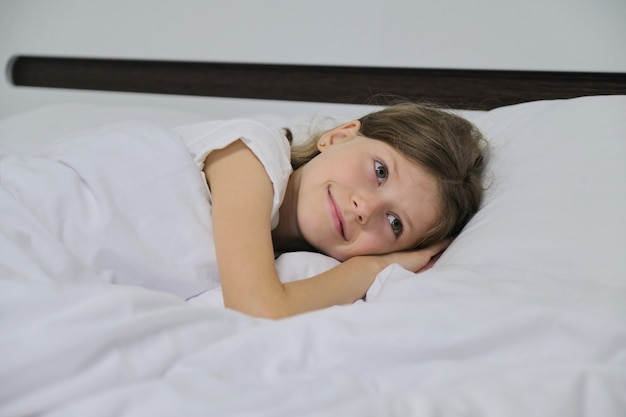 Smiling beautiful child girl lying on a pillow, white bed, close-up face