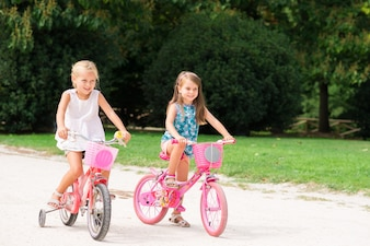 Smiling beautiful children riding on their bike