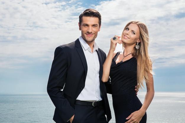 Улыбающаяся красивая пара, стоящая вместе с морем на стене