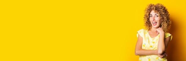 明るい黄色の背景に美しい縮れ毛の若い女性の笑顔