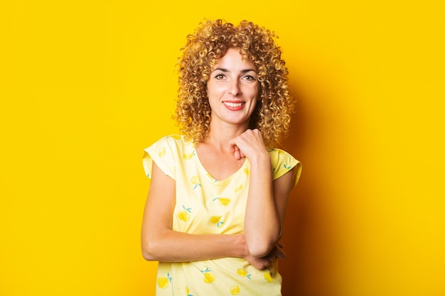 黄色の背景に美しいかわいい縮れ毛の若い女性の笑顔