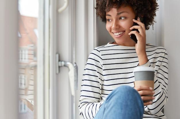 Sorridente bella donna dalla pelle scura parla sul dispositivo smart phone, detiene il caffè da asporto