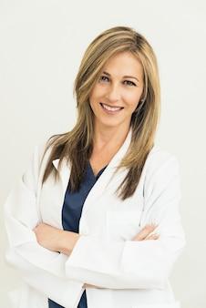 病院で美しい医者の笑顔。立っている。カメラを見てください。