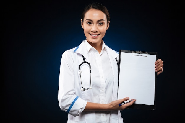 Smiling beautiful doctor showing blank clipboard isolated over black