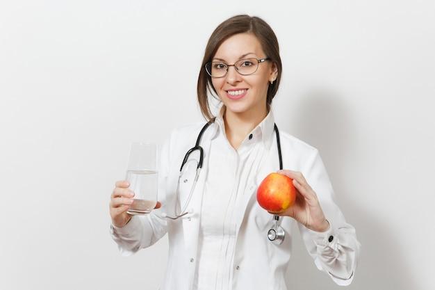 Усмехаясь красивая женщина доктора со стетоскопом, очками, изолированными на белом фоне. женщина-врач в медицинском халате, держа стакан воды, красное яблоко. медицинский персонал, здоровье, концепция медицины.