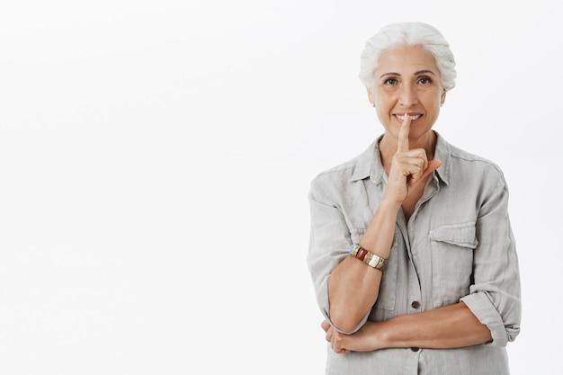 Smiling beautiful elder woman showing shush gesture, tell secret, hushing over white background