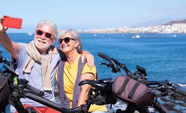 Улыбается красивая пожилая пара, сидя на скале, принимая селфи с помощью смартфона. активные пенсионеры, наслаждающиеся здоровым образом жизни и свободой на велосипедах - горизонт над водой