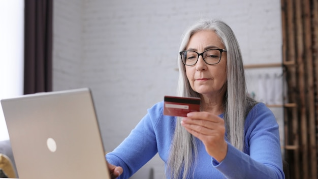 Smiling beautiful elderly gray-haired woman shopping online holding credit card.