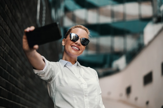 Smiling beautiful fashionable businesswoman with sunglasses standing outside and taking selfie. business center exterior.