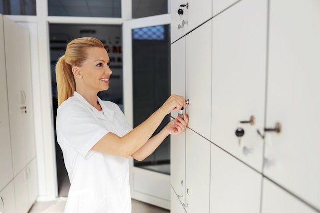 Smiling beautiful female blond assistant standing and unlocking locker in dressing room.