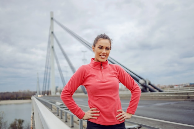 Улыбающаяся красивая подтянутая спортсменка, стоящая на мосту в пасмурный осенний день с руками на бедрах