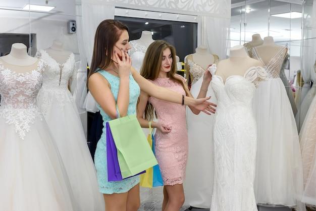 店でウェディングドレスを選ぶ美しい友人の笑顔