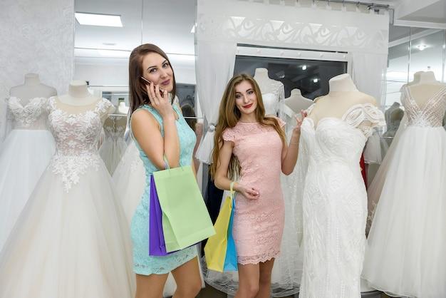 Улыбающиеся красивые друзья выбирают свадебное платье в магазине