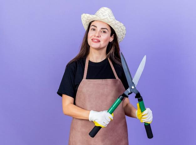 青い背景で隔離のクリッパーズを保持しているガーデニング帽子と手袋を身に着けている制服を着た美しい庭師の女の子の笑顔