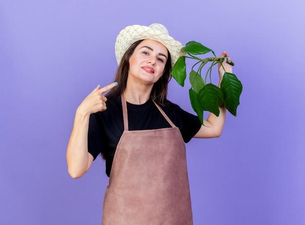 笑顔の美しい庭師の女の子の制服を着て園芸帽子を保持し、青い背景で隔離の植物を指す