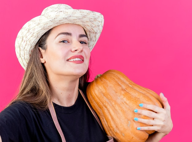 Улыбающаяся красивая девушка-садовник в униформе в садовой шляпе, держащая камеру, кладет тыкву на плечо, изолированную от розового