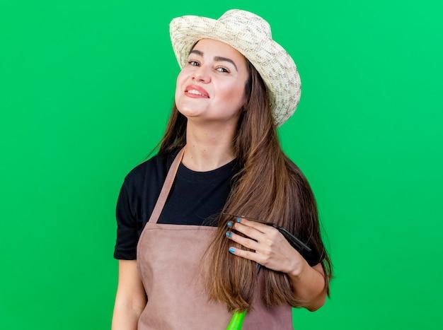 Улыбающаяся красивая девушка-садовник в униформе в садовой шляпе держит грабли с мотыгой на зеленом фоне