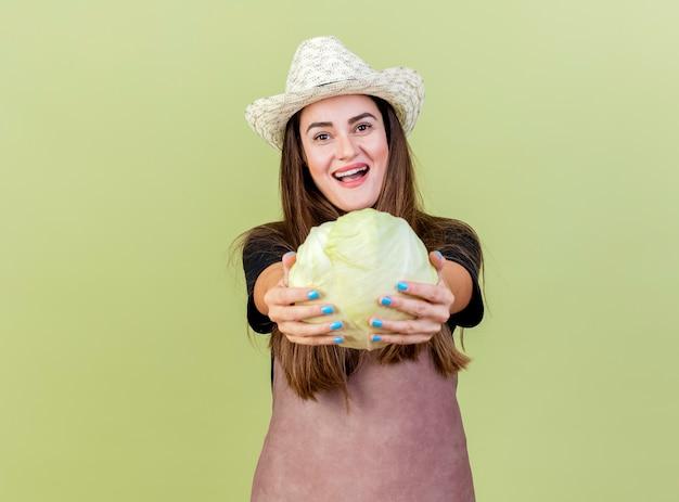 올리브 녹색 배경에 고립 된 카메라에서 양배추를 들고 원예 모자를 쓰고 제복을 입은 아름다운 정원사 소녀 미소