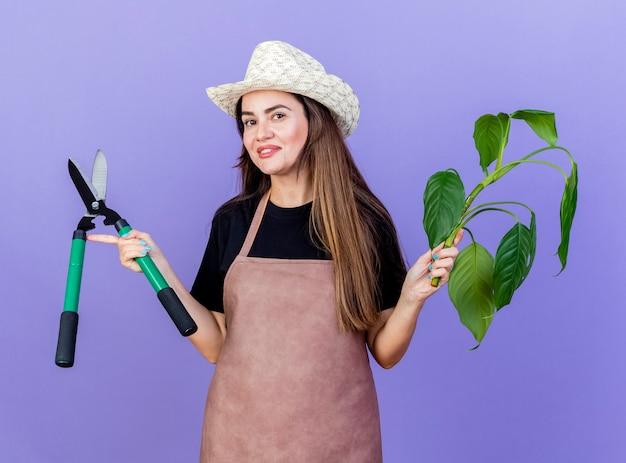 Улыбающаяся красивая девушка-садовник в униформе в садовой шляпе держит растение с кусачками и разводит руками, изолированными на синем