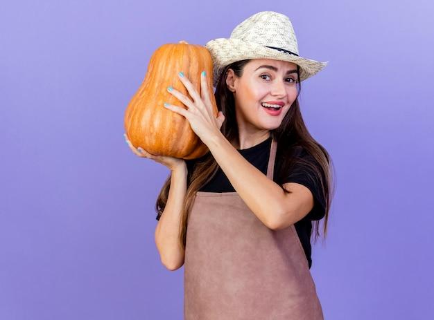 Улыбающаяся красивая девушка-садовник в униформе в садовой шляпе держит тыкву вокруг лица, изолированную на синем