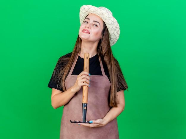 Улыбающаяся красивая девушка-садовник в униформе в садовой шляпе держит грабли на зеленом