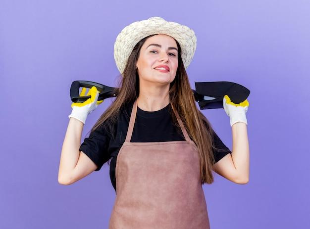 Sorridente bella ragazza giardiniere in uniforme indossando guanti e cappello da giardinaggio tenendo la vanga dietro il collo isolato su sfondo blu