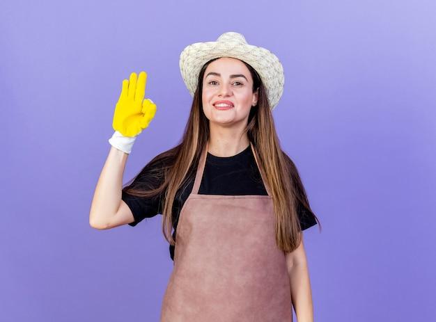 Sorridente bella ragazza giardiniere in uniforme che indossa cappello da giardinaggio e guanti che mostrano okey gesto isolato sull'azzurro