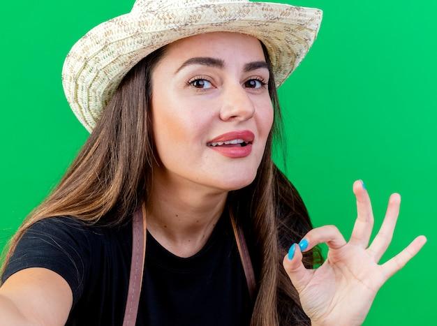 Sorridente bella ragazza giardiniere in uniforme che indossa il cappello da giardinaggio tenendo la fotocamera e mostrando okey gesto isolato su verde