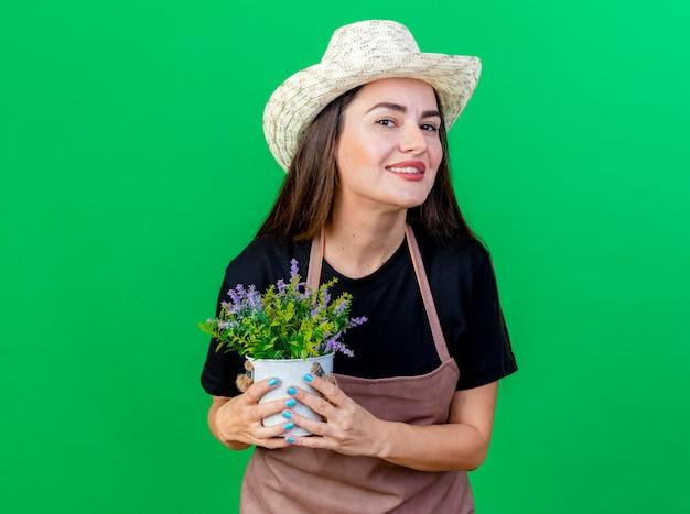 Sorridente bella ragazza giardiniere in uniforme che indossa cappello da giardinaggio tenendo il fiore in vaso di fiori isolato su verde