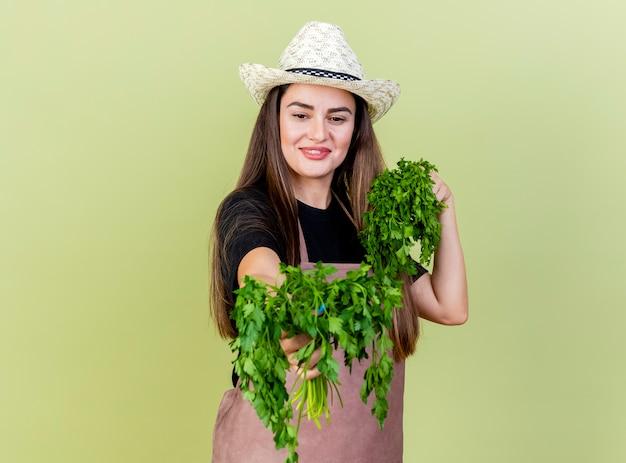 Sorridente bella ragazza giardiniere in uniforme che indossa il cappello da giardinaggio tenendo fuori il coriandolo alla macchina fotografica isolata su sfondo verde oliva