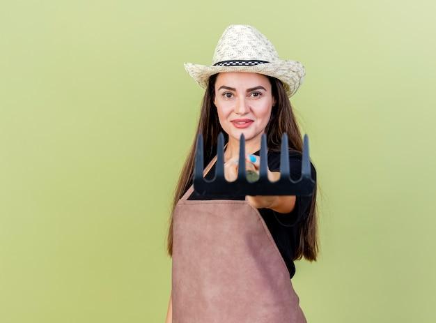 Sorridente bella ragazza giardiniere in uniforme che indossa il cappello da giardinaggio tenendo fuori il rastrello alla macchina fotografica isolata su sfondo verde oliva