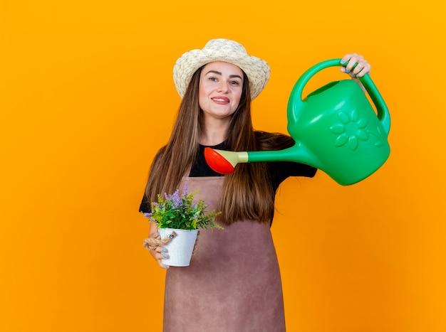 Улыбающаяся красивая девушка-садовник в униформе и садовой шляпе, поливающая цветок в горшке с лейкой, изолирована на оранжевом фоне