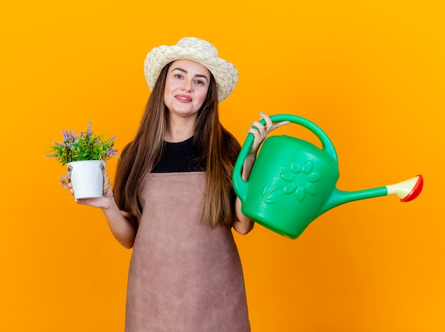 Smiling beautiful gardener girl wearing uniform and gardening hat holding watering can with flower in flwerpot isolated on orange background