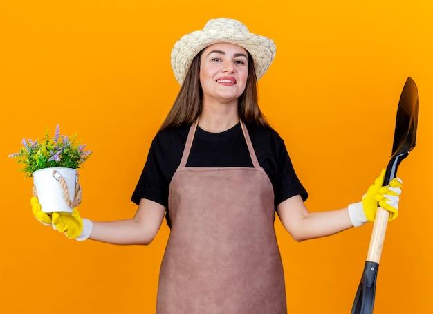 Sorridente bella ragazza giardiniere che indossa uniforme e cappello da giardinaggio con guanti che tengono vanga con fiore in vaso di fiori e diffondendo le mani isolate su priorità bassa arancione
