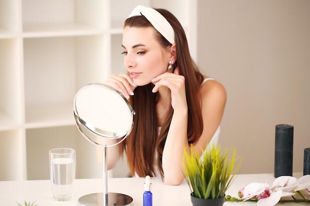 笑顔の美しい少女が顔のスキンクリームを塗って鏡を見る