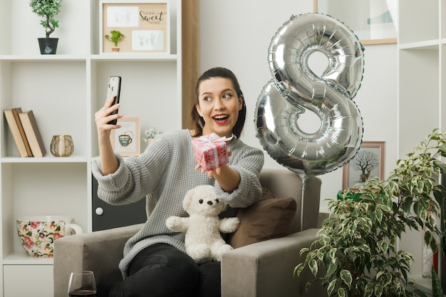 La bella ragazza sorridente nel giorno delle donne felici che tiene il presente prende un selfie seduto sulla poltrona nel soggiorno