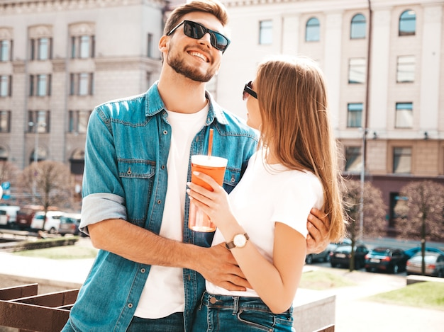 Smiling beautiful girl and her handsome boyfriend in casual summer clothes.   . woman with bottle of water
