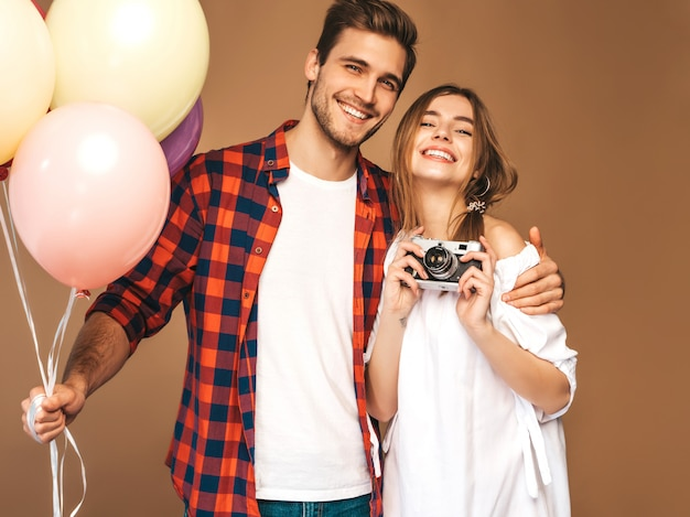 Smiling beautiful girl and her handsome boyfriend holding bunch of colorful balloons. happy couple taking photo selfie of themselves on retro camera. happy birthday