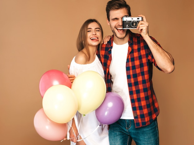 Smiling beautiful girl and her handsome boyfriend holding bunch of colorful balloons. happy couple taking photo of themselves on retro camera. happy birthday