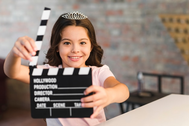 Smiling beautiful girl holding clapperboard