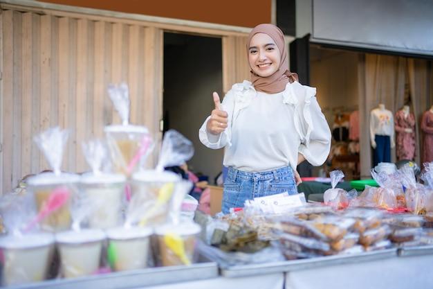 Улыбающаяся красивая девушка в хиджабе с большими пальцами руки предлагает разнообразную еду, съеденную после прекращения поста