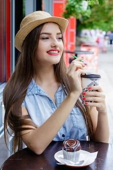 머핀으로 커피를 마시는 야외 카페에서 웃는 아름 다운 소녀