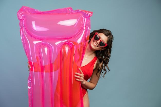 笑顔、サングラス、水着、ピンクのエアマットレスを保持している美しい少女