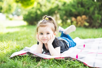 Smiling beautiful girl lying on blanket over the green grass